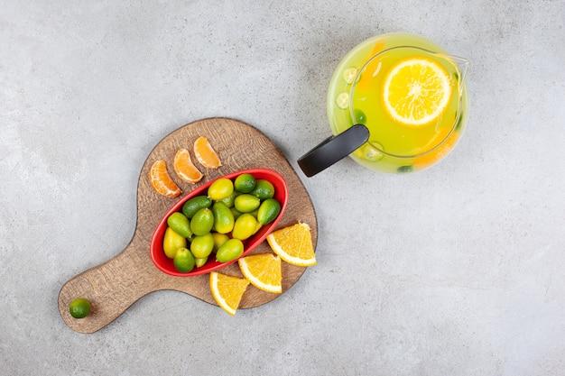 Bovenaanzicht van vers fruit limonade met een stapel kumquats met sinaasappel- en mandarijnplakken op een houten bord.