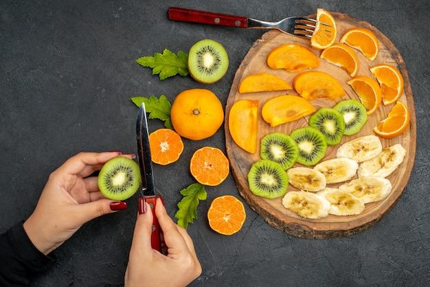 Bovenaanzicht van vers fruit op een houten dienblad, hand met een sinaasappel op een zwarte ondergrond