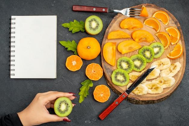 Bovenaanzicht van vers fruit op een houten dienblad, hand met een sinaasappel op zwarte tafel