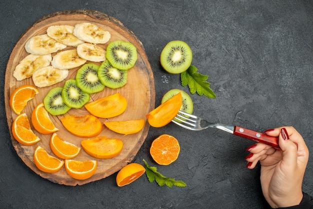 Bovenaanzicht van vers fruit op een houten dienblad, hand met een vork met een schijfje kiwi's op een donkere achtergrond