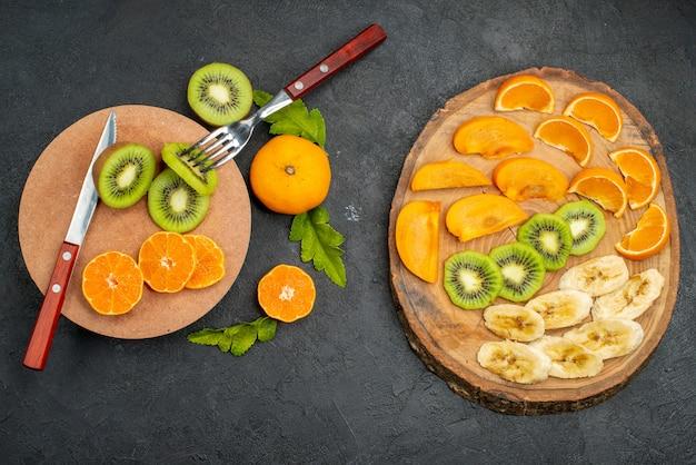 Bovenaanzicht van vers fruit op snijplank en houten dienblad op donkere achtergrond