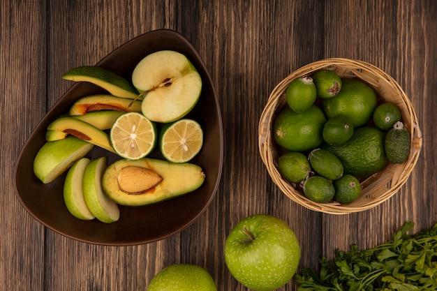 Bovenaanzicht van vers fruit plakjes zoals appels avocado's limoenen op een kom met feijoas en limoenen op een emmer met appels en peterselie geïsoleerd op een houten achtergrond
