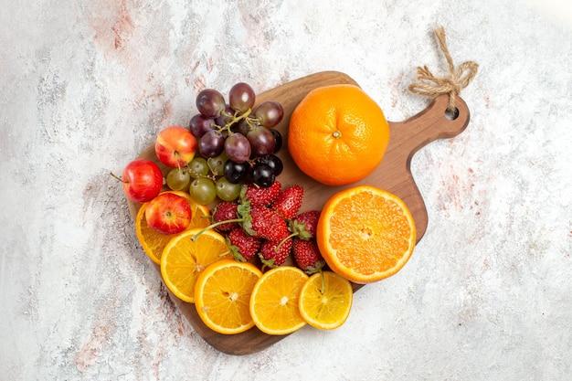 Bovenaanzicht van vers fruit samenstelling sinaasappelen druiven en aardbeien op witte ondergrond