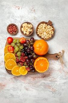 Bovenaanzicht van vers fruit samenstelling verse sinaasappelen druiven noten en aardbeien op witte ondergrond