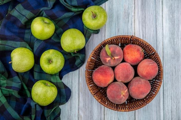 Bovenaanzicht van vers fruit zoals appels op geruit tafelkleed en perziken op emmer op grijs hout