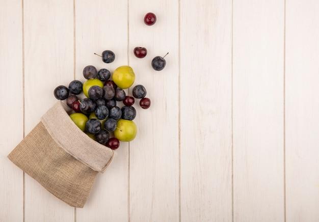 Bovenaanzicht van vers fruit zoals donkerpaarse sloesred kersen en groene kersenpruim vallen uit een jute zak op witte houten achtergrond met kopie ruimte