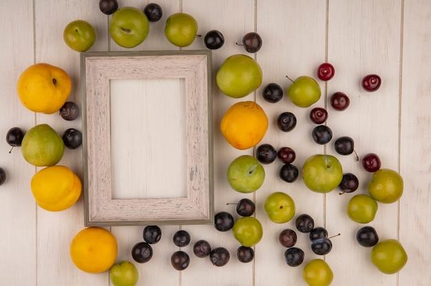 Bovenaanzicht van vers fruit zoals gele perziken, groene kersen, pruimen, rode kersen op een witte houten achtergrond met kopie ruimte