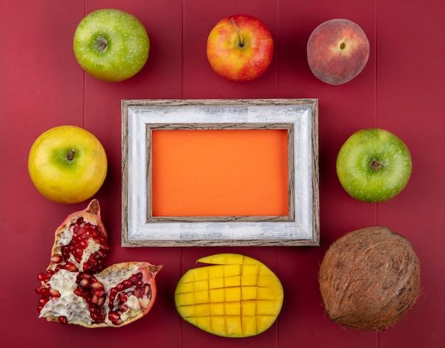 Bovenaanzicht van vers fruit zoals gesneden mango granaatappel zaden appels perziken en kokos op rood