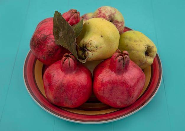 Bovenaanzicht van vers fruit zoals granaatappel kweepeer en appels op een kom op een blauwe achtergrond