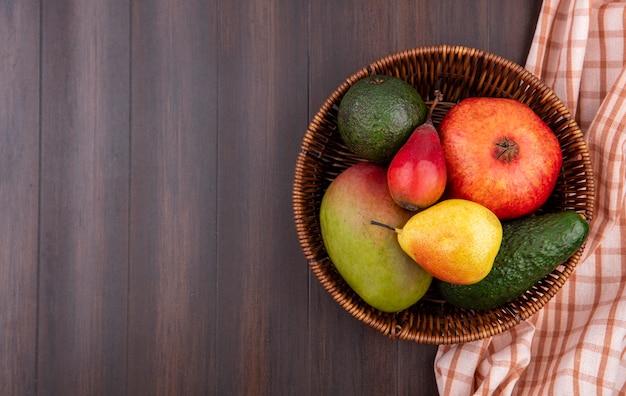 Bovenaanzicht van vers fruit zoals granaatappel peer mango op emmer op hout met kopie ruimte