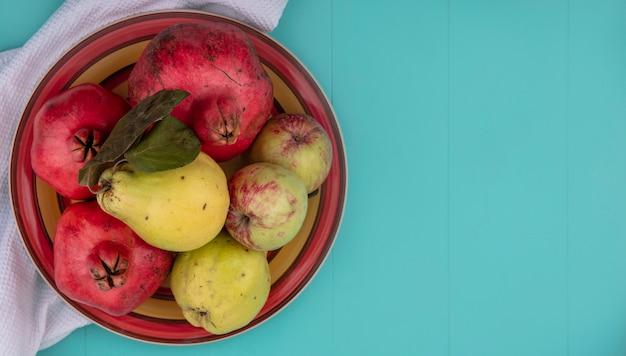 Bovenaanzicht van vers fruit zoals granaatappelkweepeer en appels op een kom op een witte doek op een blauwe achtergrond met kopie ruimte