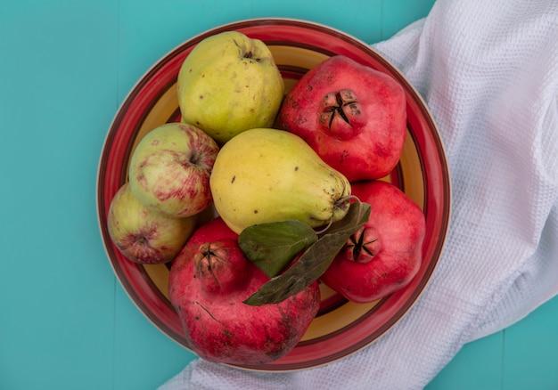 Bovenaanzicht van vers fruit zoals granaatappelkweepeer en appels op een kom op een witte doek op een blauwe achtergrond