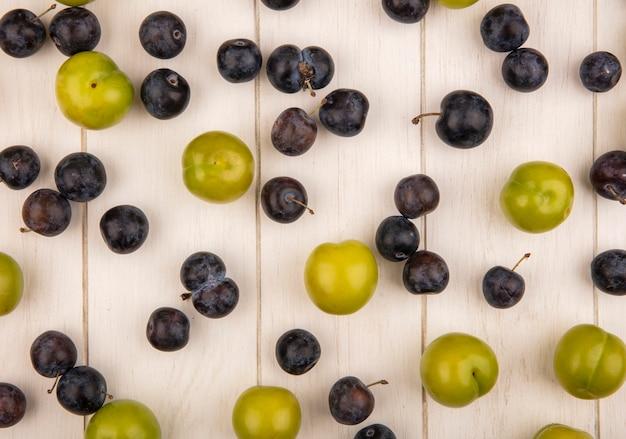 Bovenaanzicht van vers fruit zoals groene kersenpruim en donkerpaarse sleepruimen geïsoleerd op een witte houten achtergrond