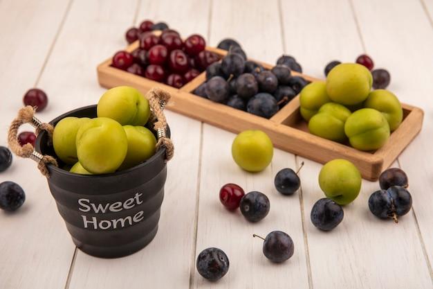 Bovenaanzicht van vers fruit zoals groene kersenpruimen, rode kersen en sleepruimen op een houten onderverdeeld dienblad met groene kersenpruim op een mand op een witte achtergrond