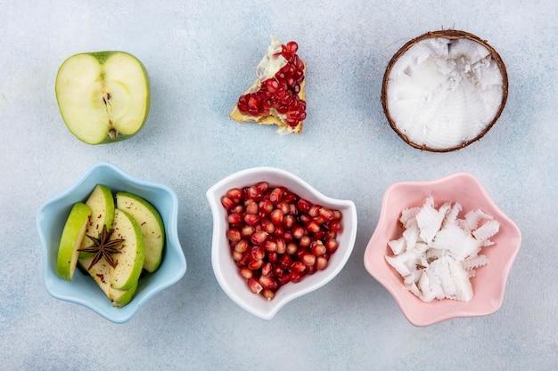 Bovenaanzicht van vers fruit zoals halve groene appel met gehakte appelschijfjes met granaatappelpitjes in een witte kom en kokos met pulp van kokos in een roze kom op wit