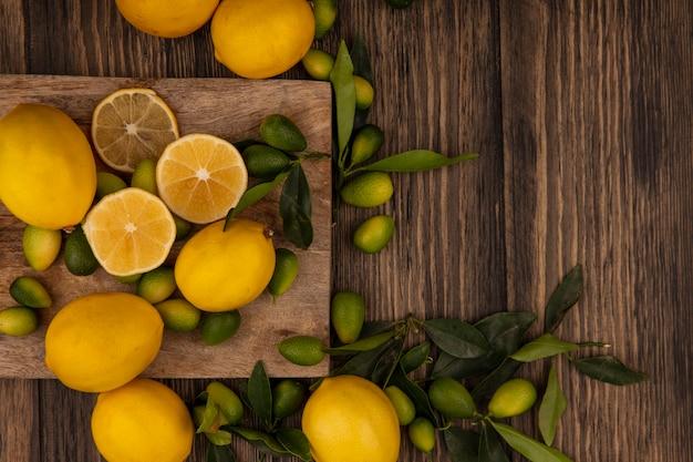Bovenaanzicht van vers fruit zoals kinkans en citroenen geïsoleerd op een houten keukenbord op een houten muur met kopie ruimte