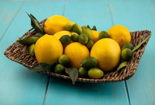 Bovenaanzicht van vers fruit zoals kinkans en citroenen op een rieten dienblad op een blauwe houten muur