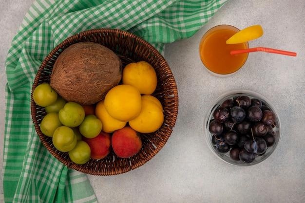Bovenaanzicht van vers fruit zoals kokos perzik groene kersenpruimen op een emmer op een geruite doek met sleepruimen op een kom met vers perziksap op een witte achtergrond