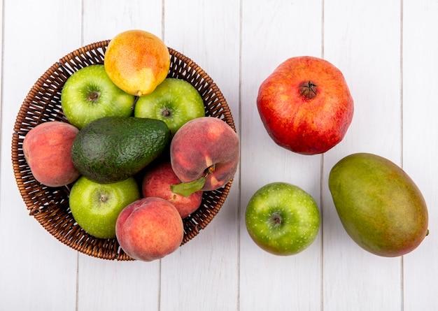 Bovenaanzicht van vers fruit zoals perzik peer appel op emmer met granaatappel avocado op wit