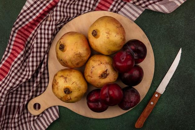 Bovenaanzicht van vers fruit zoals plukken en granaatappels op een houten keukenbord op een geruite doek met mes op een groen oppervlak