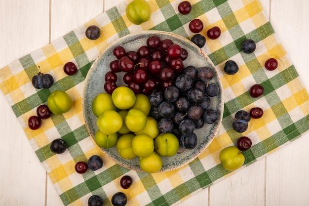 Bovenaanzicht van vers fruit zoals rode kersen donkerpaarse slees, groene kersenpruimen op een kom op een gecontroleerd tafellaken op een witte houten achtergrond