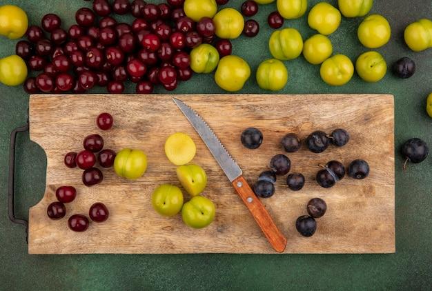Bovenaanzicht van vers fruit zoals rode kersen, groene kersenpruim, donkere paarse sleepruimen op een houten keukenbord met mes met rode kersen geïsoleerd op een groene achtergrond