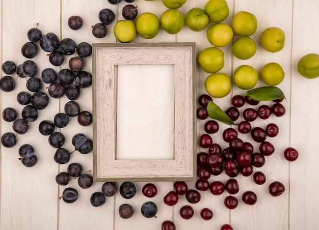 Bovenaanzicht van vers fruit zoals sloescherries en groene kersenpruimen geïsoleerd op een witte achtergrond met kopie ruimte