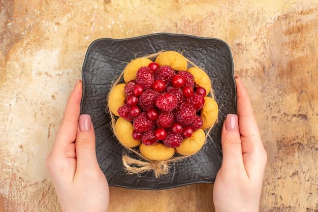 Bovenaanzicht van vers gebakken cadeau cake op een bruine plaat op gemengde kleur achtergrond