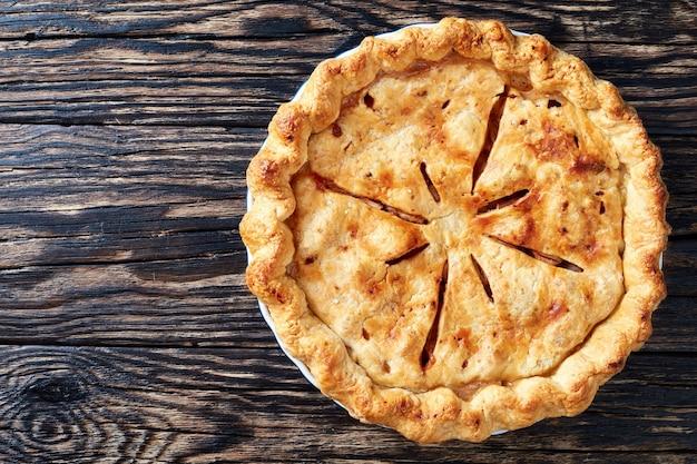 Bovenaanzicht van vers gebakken heerlijke klassieke zelfgemaakte amerikaanse appeltaart op een oude rustieke houten planken, weergave van bovenaf, kopieer ruimte, flatlay