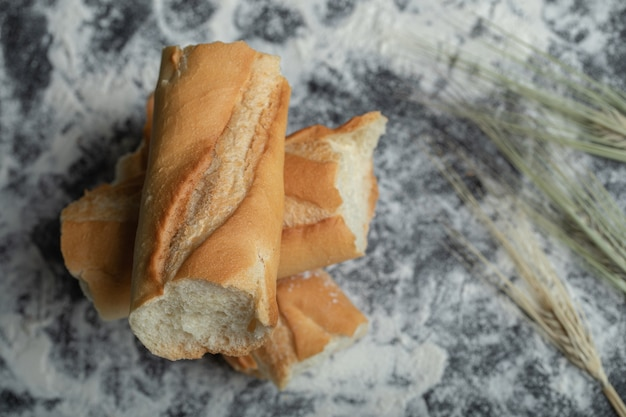 Bovenaanzicht van vers gebakken stokbrood plakjes op witte achtergrond.