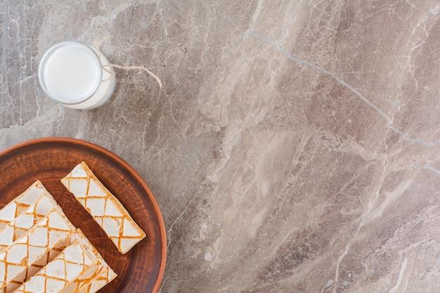 Bovenaanzicht van vers gebakken wafels met melk op grijs.