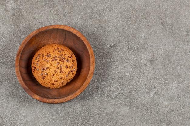 Bovenaanzicht van vers gebakken zelfgemaakt koekje in houten kom.