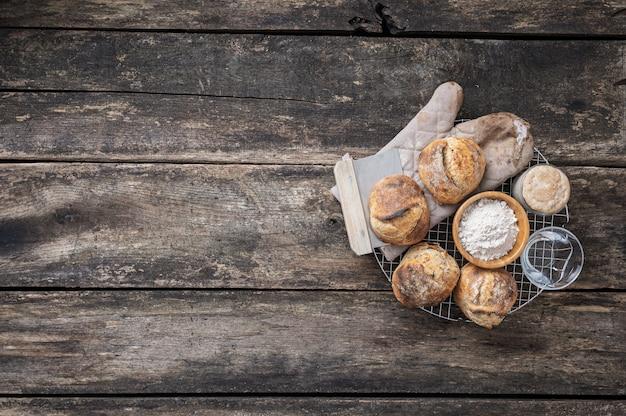 Bovenaanzicht van vers gebakken zuurdesembroodjes op rustieke houten planken
