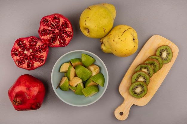 Bovenaanzicht van vers gehakte appelschijfjes op een kom met plakjes kiwi op een houten keukenbord met granaatappels en kweeperen geïsoleerd