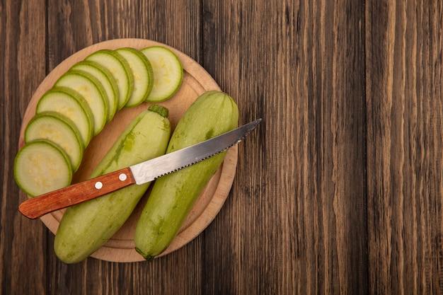 Bovenaanzicht van vers gehakte courgettes op een houten keukenbord met mes op een houten muur met kopie ruimte