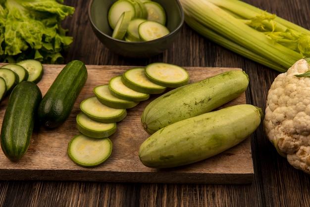 Bovenaanzicht van vers gehakte komkommers en courgettes geïsoleerd op een houten keukenbord met sla selderij en bloemkool geïsoleerd op een houten achtergrond