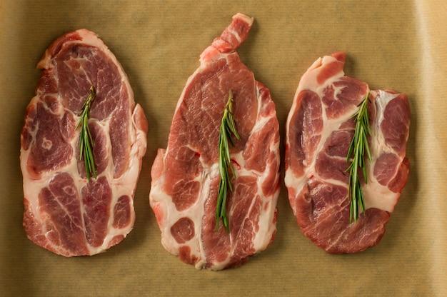 Bovenaanzicht van vers gehakte varkensvlees steakes met rozemarijn op bakpapier klaar om te koken. koken en culinair.