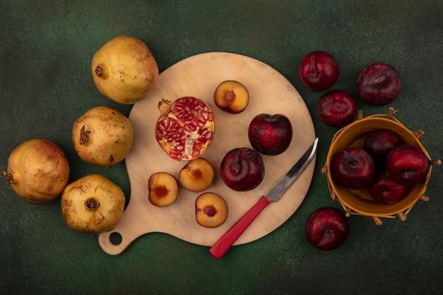 Bovenaanzicht van vers gehalveerd fruit zoals plukken en granaatappels op een houten keukenbord met mes op een groene achtergrond
