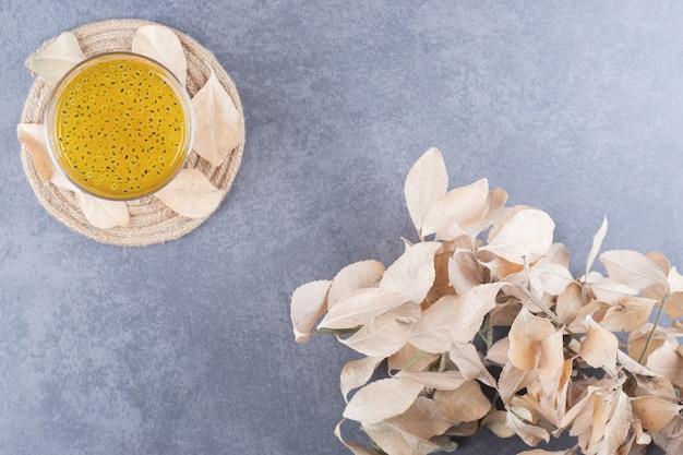Bovenaanzicht van vers gemaakt sinaasappelsap met decoratieve bladeren op grijze achtergrond.