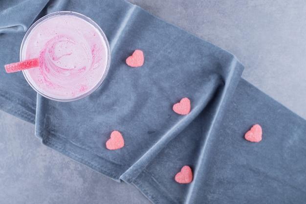 Bovenaanzicht van vers gemaakte roze milkshake op grijze achtergrond.
