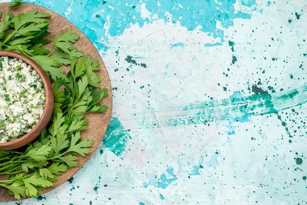 Bovenaanzicht van vers gesneden koolsalade met greens in bruine kom op helderblauw