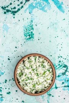 Bovenaanzicht van vers gesneden koolsalade met greens in bruine kom op helderblauwe, groene de versheidssnack van de voedselgroente salade