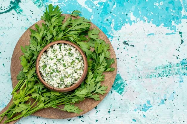 Bovenaanzicht van vers gesneden koolsalade met greens in bruine kom op helderblauwe, groene snack van de groentesalade