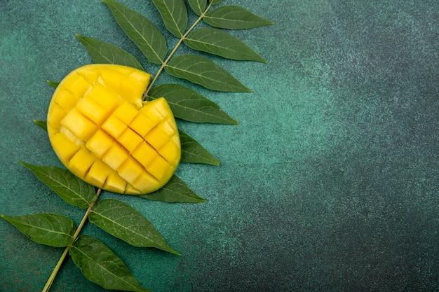 Bovenaanzicht van vers gesneden mango met blad op groen