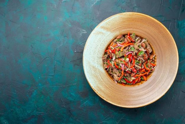Bovenaanzicht van vers gesneden salade met vlees in plaat op donkerblauw, salade eten maaltijd vlees lunch