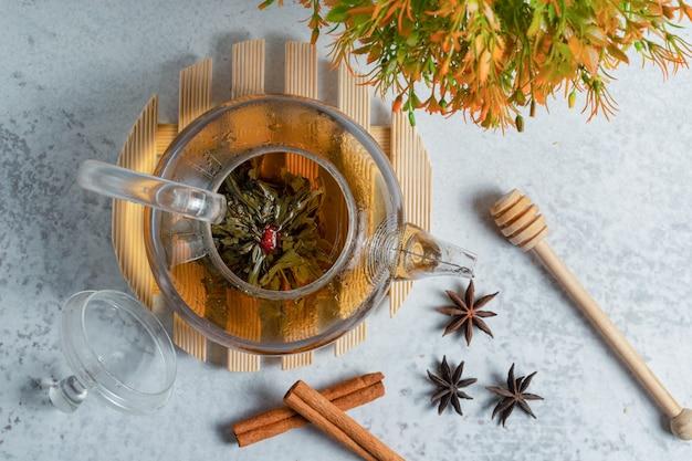 Bovenaanzicht van vers gezette thee op grijze ondergrond.