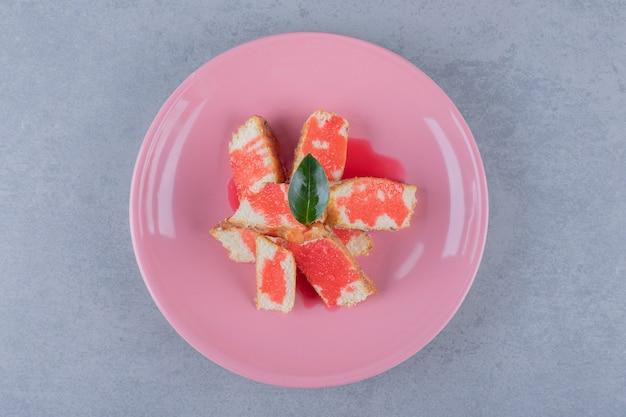 Bovenaanzicht van vers koekje met saus op roze plaat