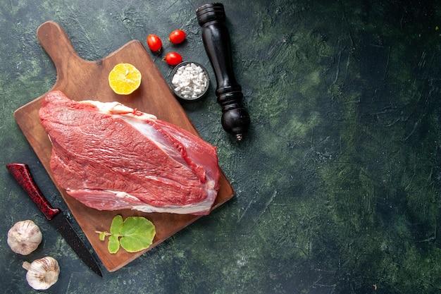 Bovenaanzicht van vers rauw rood vlees citroen op bruin houten snijplank en mes groenten houten hamer op donkere kleur achtergrond