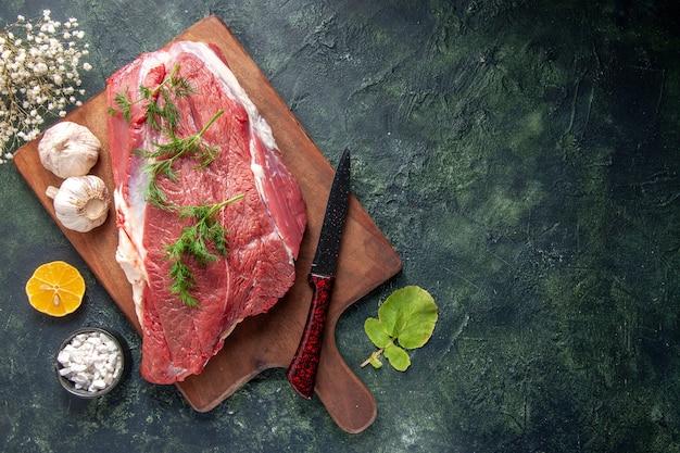 Bovenaanzicht van vers rauw rood vlees groen knoflookmes op bruin houten snijplank zout citroen aan de rechterkant op donkere kleur achtergrond