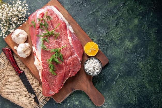 Bovenaanzicht van vers rauw rood vlees groene knoflook citroenzout op bruin houten snijplank mes op naakt kleur handdoek op donkere kleur achtergrond